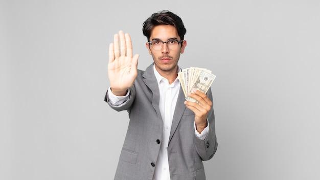 Młody latynoski mężczyzna wyglądający poważnie, pokazując otwartą dłoń, wykonując gest zatrzymania