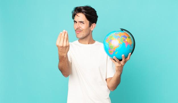 Młody latynoski mężczyzna wykonujący gest kaprysu lub pieniędzy, mówiący ci, aby zapłacić i trzymając mapę świata