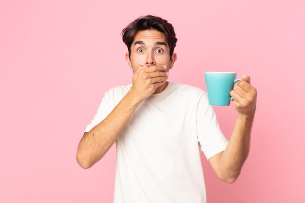 Młody latynoski mężczyzna zakrywający usta dłońmi zszokowany i trzymający kubek z kawą