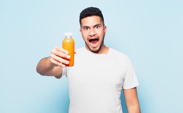 Młody latynoski mężczyzna zaskoczony wyrazem twarzy i trzymający koktajl
