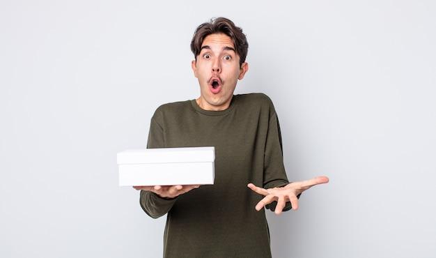 Młody latynoski mężczyzna zdumiony, zszokowany i zdumiony niewiarygodną niespodzianką. koncepcja białego pudełka