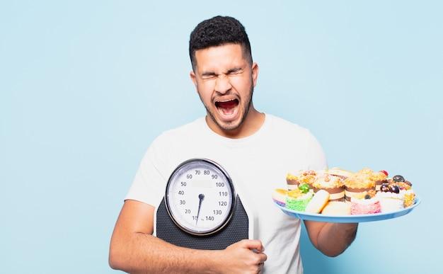 Młody latynoski mężczyzna zły wyraz twarzy i koncepcja diety