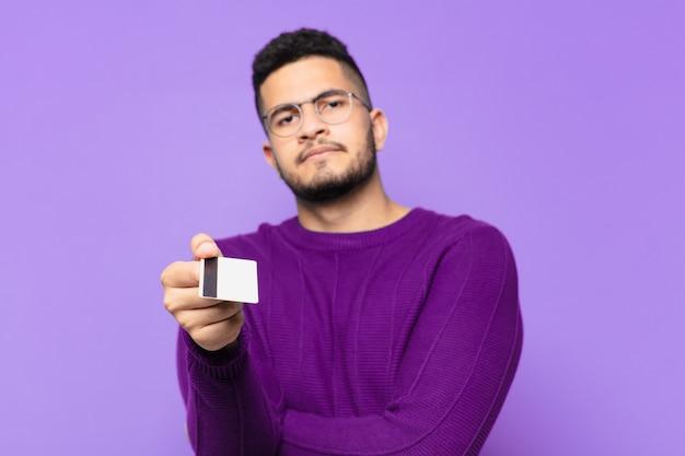 Młody latynoski mężczyzna zły wyraz twarzy i trzymający kartę kredytową