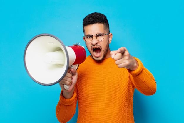 Młody latynoski mężczyzna zły wyraz twarzy i trzymający megafon