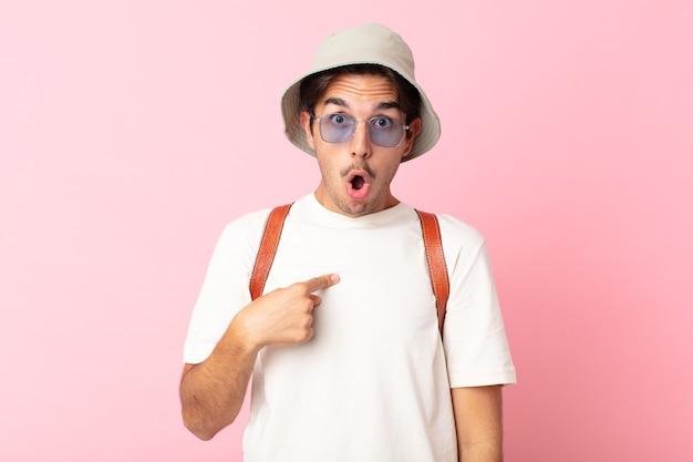 Młody latynoski mężczyzna, zszokowany i zaskoczony, z szeroko otwartymi ustami, wskazując na siebie. koncepcja lato