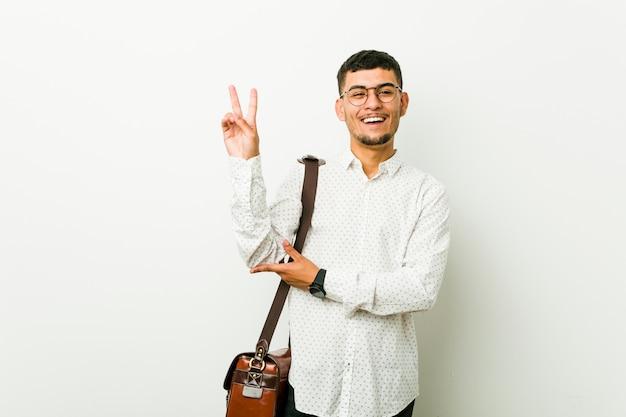 Młody latynoski przypadkowy biznesowy mężczyzna pokazuje numer dwa z palcami
