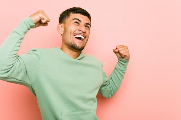 Młody latynoski sporta mężczyzna dźwigania pięść po zwycięstwa, zwycięzcy pojęcie.
