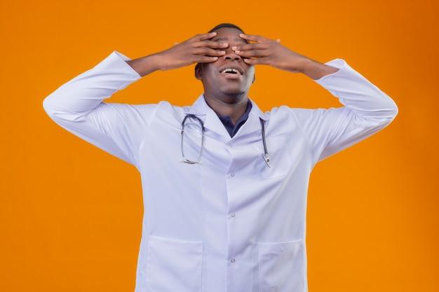 Młody lekarz afroamerykanin ubrany w biały fartuch ze stetoskopem obejmującym oczy rękami