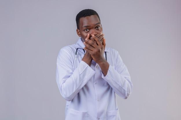 Młody lekarz afroamerykanin ubrany w biały fartuch ze stetoskopem, patrząc zdumiony i zszokowany, zakrywając usta rękami