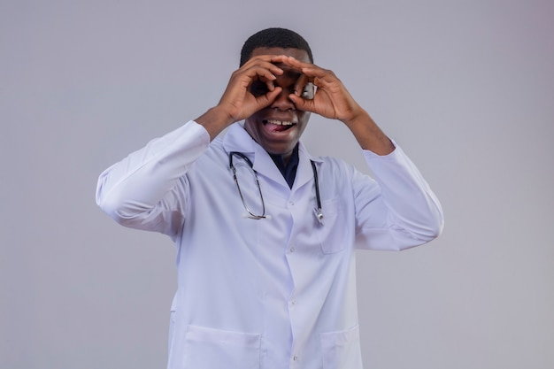 Młody lekarz afroamerykanin ubrany w biały fartuch ze stetoskopem robi ok gest jak lornetka patrząc przez palce wystające język