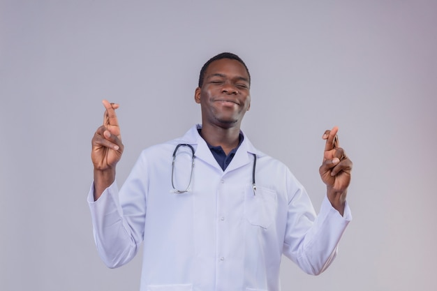 Młody lekarz afroamerykanin ubrany w biały fartuch ze stetoskopem trzymając strzykawkę czyniąc pożądane życzenie z zamkniętymi oczami krzyżującymi palcami