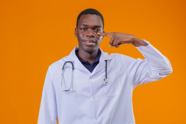 Młody lekarz afroamerykanin ubrany w biały fartuch ze stetoskopem wskazującym palcem na oko, uśmiechając się i czekając