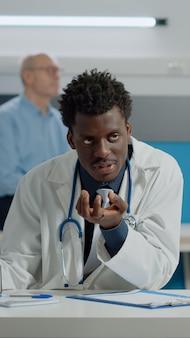 Młody lekarz analizujący animację wirusa na tablecie ze starą kobietą