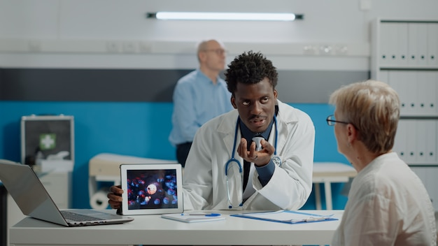 Młody lekarz analizuje animację wirusa na tablecie ze staruszką przy biurku w gabinecie lekarskim. lekarz i starszy pacjent oglądający nowoczesne urządzenie pokazujące bakterie koronawirusa i niebezpieczeństwo