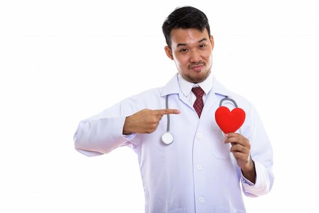 Młody lekarz człowiek azji gospodarstwa i wskazując na czerwone serce na swoim garniturze