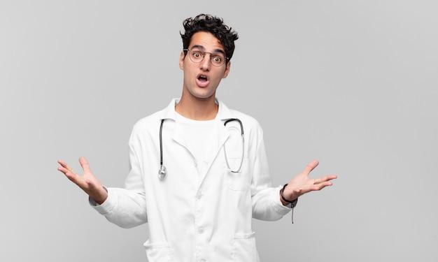 Młody lekarz czuje się niezwykle zszokowany i zaskoczony, niespokojny i spanikowany, ma zestresowany i przerażony wyraz twarzy