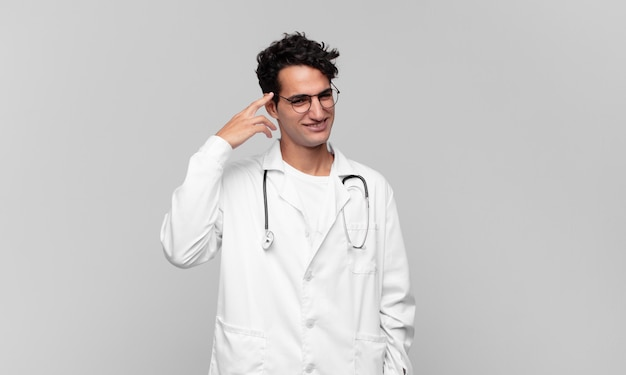 Młody lekarz czuje się zdezorientowany i zdziwiony, pokazując, że jesteś szalony, szalony lub oszalały