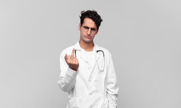 Młody lekarz czuje się zły, zirytowany, buntowniczy i agresywny, machając środkowym palcem, walczący