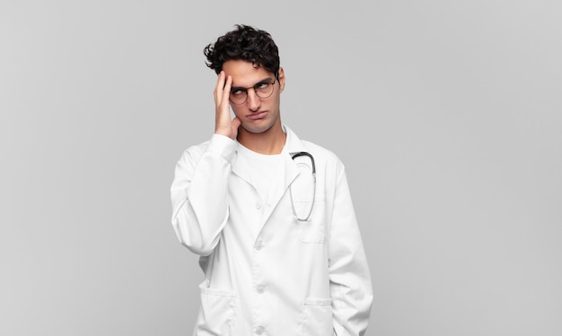 Młody lekarz czuje się znudzony, sfrustrowany i senny po męczącym, nudnym i żmudnym zadaniu, trzymając twarz ręką