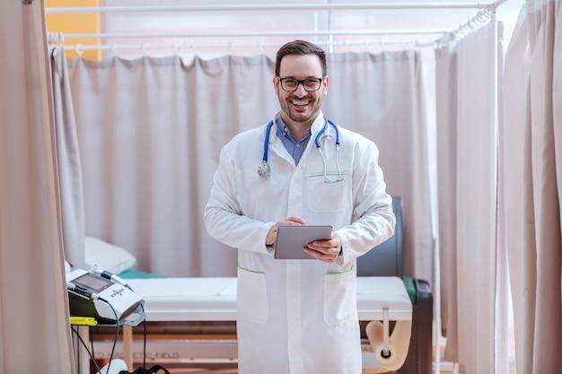 Młody lekarz kaukaski w białym mundurze uśmiechnięty, stojąc w nowoczesnym gabinecie lekarskim.