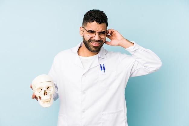 Młody lekarz łacińskiej mężczyzna trzyma czaszkę obejmujące uszy rękami.