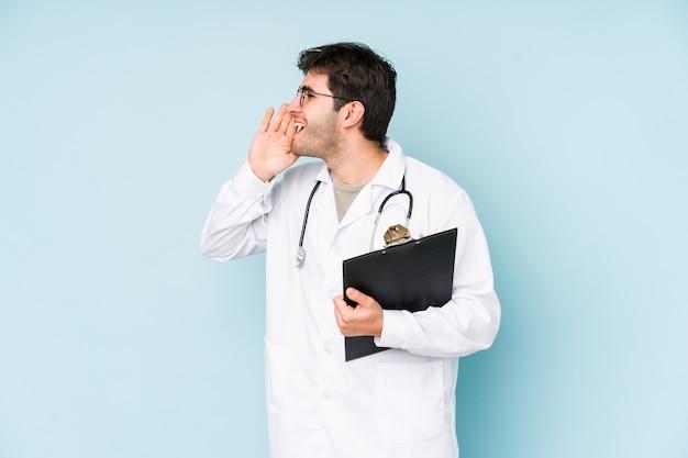 Młody lekarz mężczyzna krzyczy i trzyma dłoń w pobliżu otwartych ust.