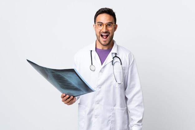 Młody lekarz mężczyzna posiadający radiografię na białym tle na białej ścianie z wyrazem twarzy zaskoczenia