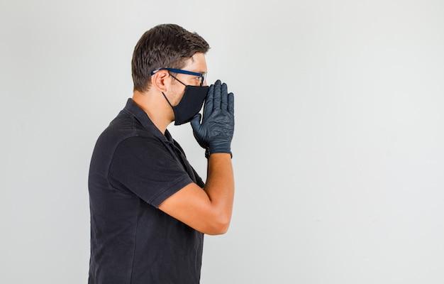 Młody lekarz modli się w czarnej koszulce polo i wygląda na zmartwionego