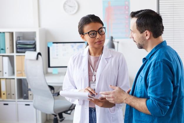 Młody lekarz omawia z pacjentem swoje sposoby leczenia, gdy stoją w biurze