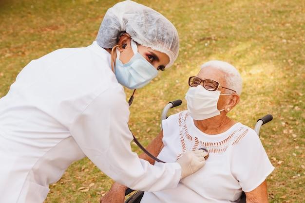 Młody lekarz opiekujący się starszą kobietą w parku
