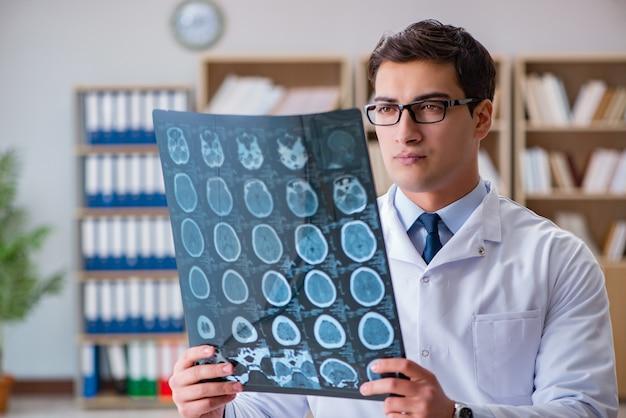 Młody lekarz patrząc na zdjęcie rentgenowskie tomografii komputerowej