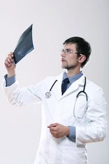 Młody lekarz patrząc na zdjęcie rentgenowskie