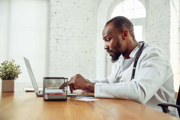 Młody lekarz podczas pracy, wyjaśniający przepisy na leki