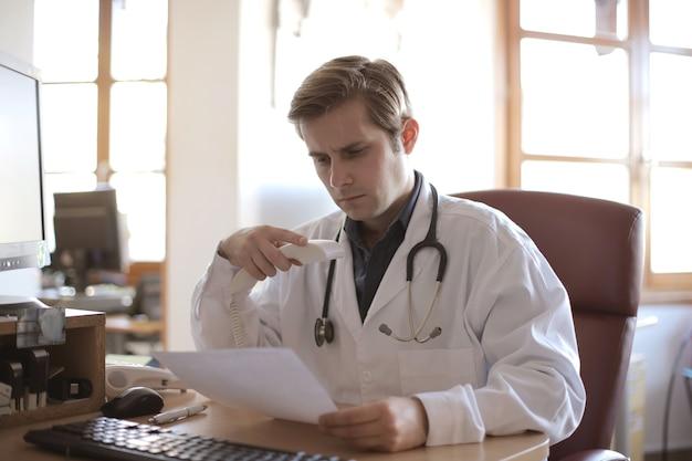 Młody lekarz pracujący w swoim biurze z oknami w tle