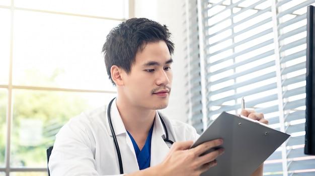 Młody lekarz pracuje w jego biurze