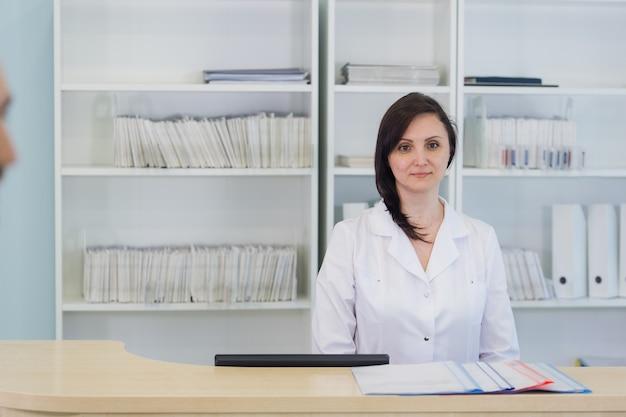 Młody lekarz praktykujący pracuje w recepcji kliniki