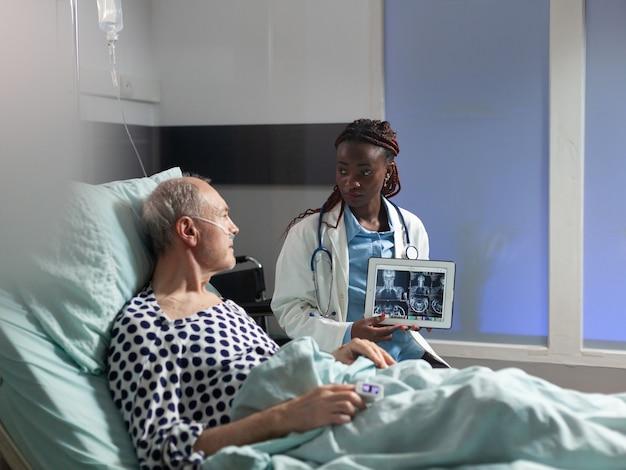 Młody lekarz siedzący obok starszego mężczyzny wyjaśniający diagnozę urazu ciała, pokazujący zdjęcie rentgenowskie na komputerze typu tablet w sali szpitalnej