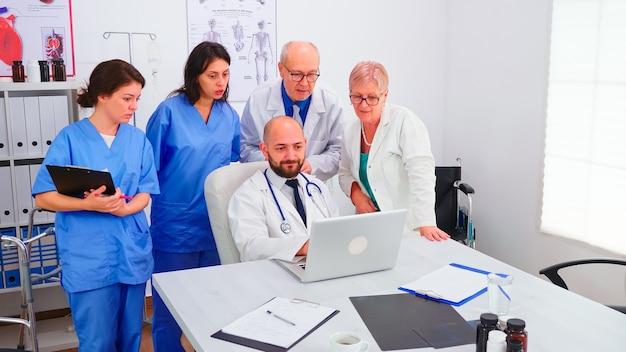 Młody lekarz specjalista informujący swój zespół medyczny w sali konferencyjnej szpitala za pomocą laptopa. zespół medyczny, osoby pracujące zespołowo omawiające diagnozę dotyczącą rejestrowania problemów z leczeniem pacjentów w miejscu pracy.
