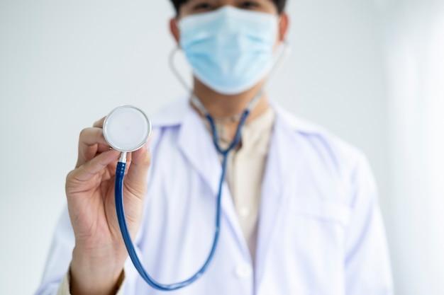 Młody lekarz trzymający stetoskop i maskę medyczną w celu ochrony przed chorobą koronawirusową lub globalną epidemią covid-19.