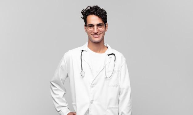 Młody lekarz uśmiechnięty radośnie, z ręką na biodrze i pewną siebie, pozytywną, dumną i przyjazną postawą