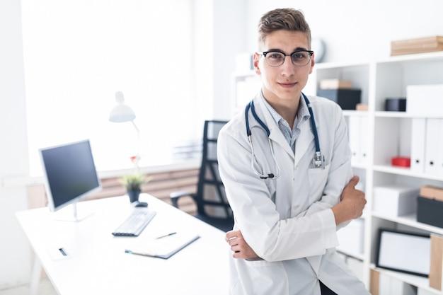 Młody lekarz w białej szacie opiera się na stole w biurze.