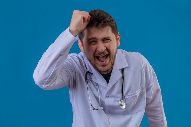 Młody lekarz w białym fartuchu i stetoskopie jest zły i szalony podnosząc pięść sfrustrowany i wściekły, krzycząc ze złości na izolowanym niebieskim tle