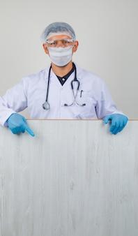 Młody lekarz w białym fartuchu, kapeluszu, rękawiczkach, pokazano drewnianą deskę