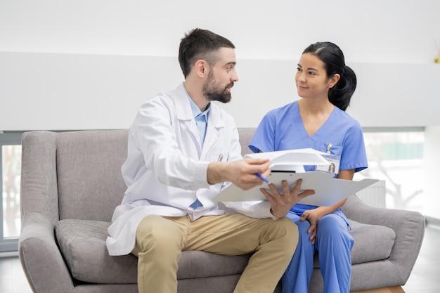 Młody lekarz w białym fartuchu wyjaśnia informacje w dokumencie swojemu ładnemu asystentowi w niebieskim mundurze, siedząc w holu kliniki