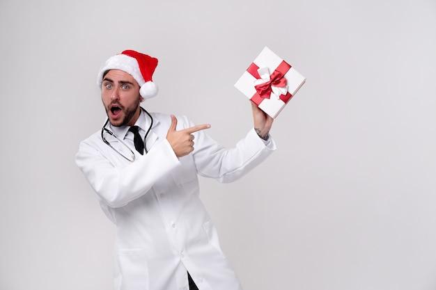 Młody lekarz w białym mundurze i czapce świętego mikołaja