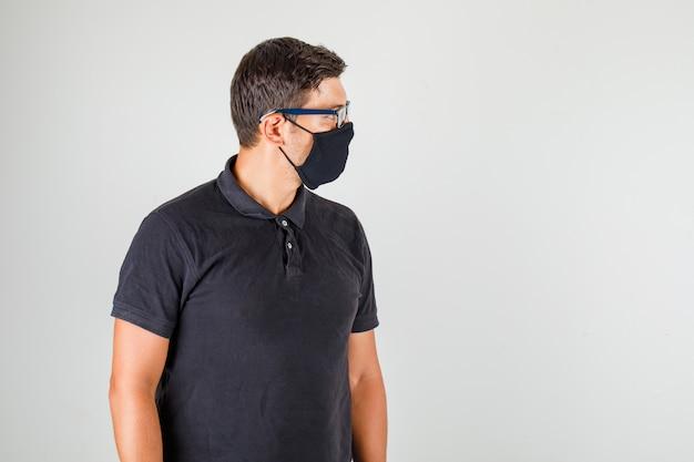 Młody lekarz w czarnej koszulce polo, patrząc na jego bok i patrząc uważnie