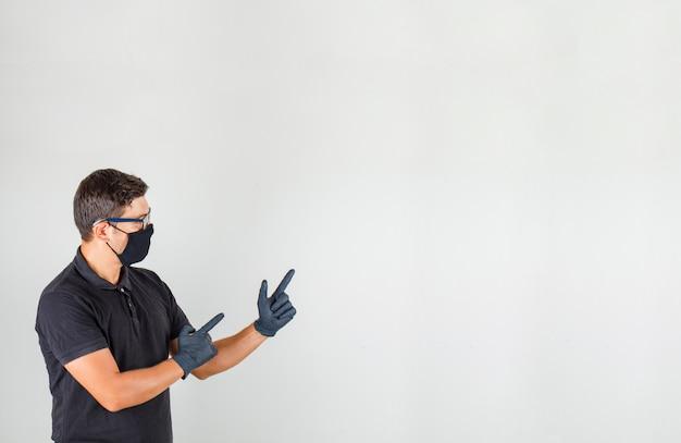 Młody lekarz w czarnej koszulce polo, wskazując palcami