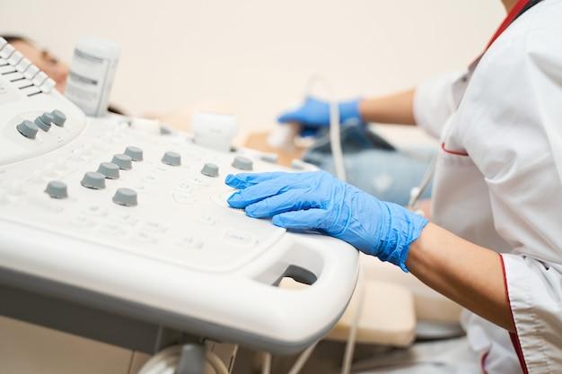 Młody lekarz w mundurze medycznym podczas korzystania z nowoczesnego sprzętu podczas kontroli zdrowia