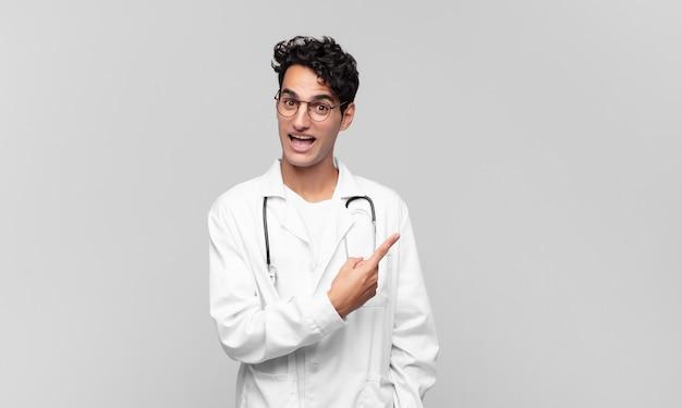 Młody lekarz wyglądający na podekscytowany i zaskoczony, wskazujący na bok i do góry, aby skopiować miejsce