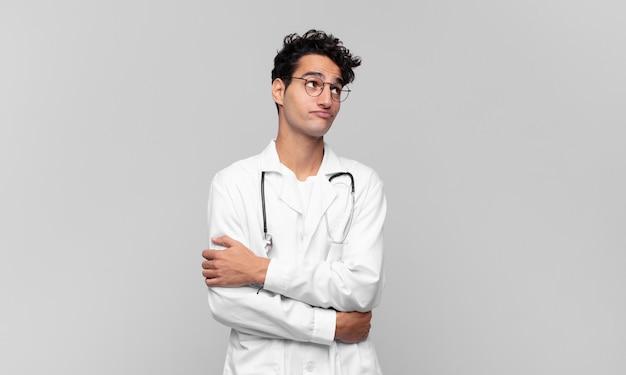 Młody lekarz wzruszający ramionami, zdezorientowany i niepewny, wątpiący z założonymi rękami i zdziwionym spojrzeniem